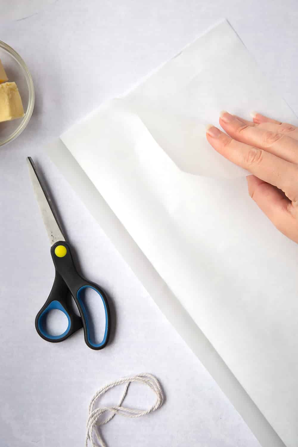 Folding the paper along its length to double the thickness of the strip. Scissors and string have been left to the side to decorate the image.