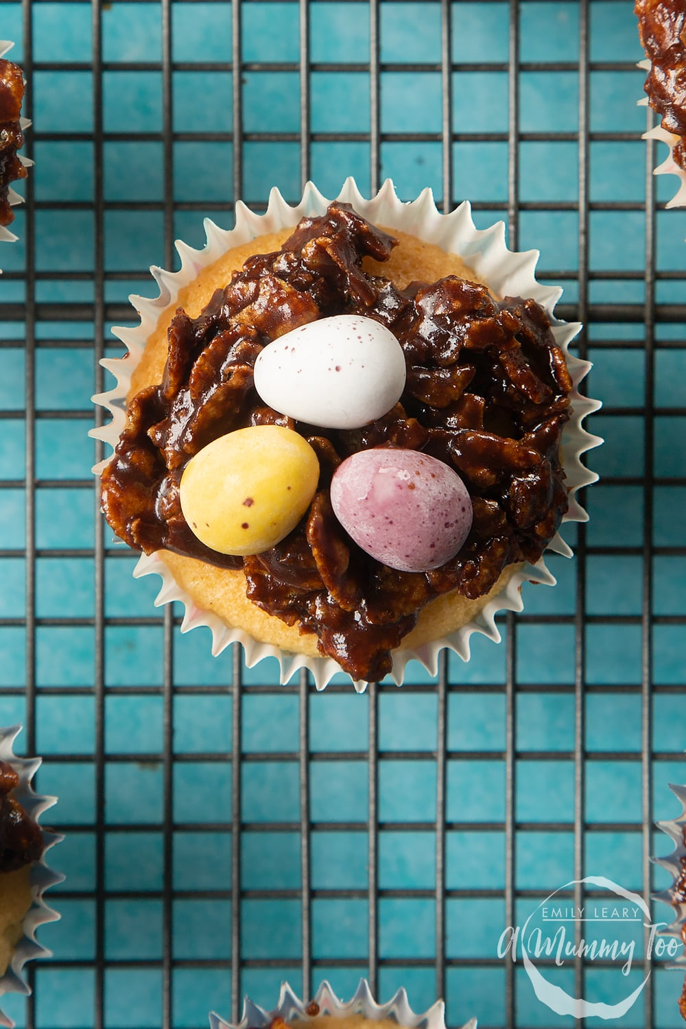 Overhead shot of easter nest cupcakes with chocolate eggs on top on a baking rack with a mummy too logo in the lower-right corner