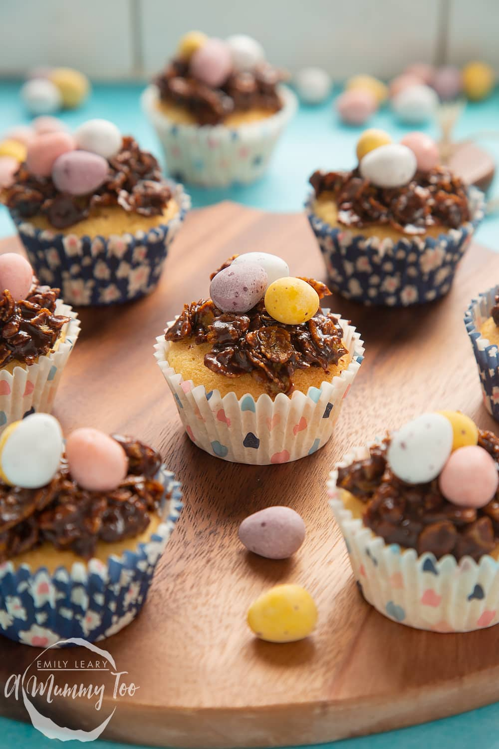 Front angle shot of chocolate easter nest cupcakes served on a wooden plate with a mummy too logo in the lower-left corner