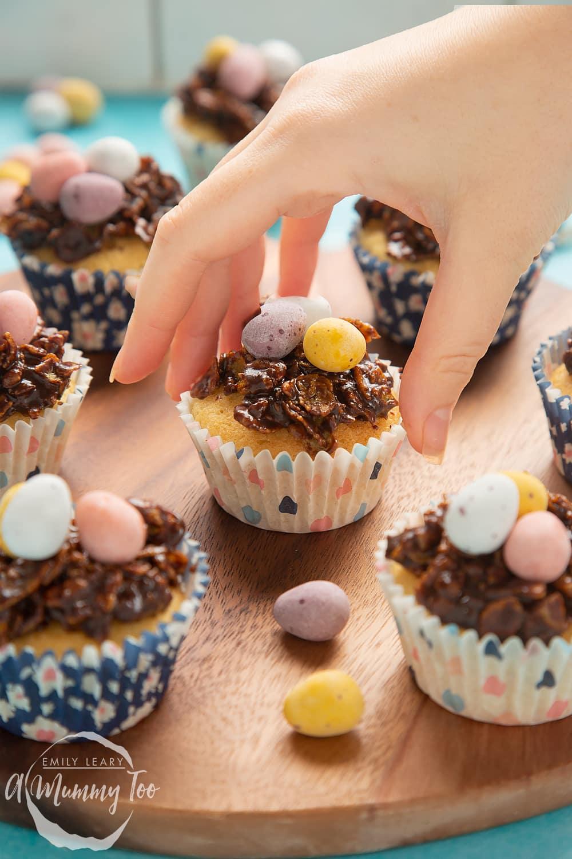 Hand reaching in grabbing an Easter cupcake nest.