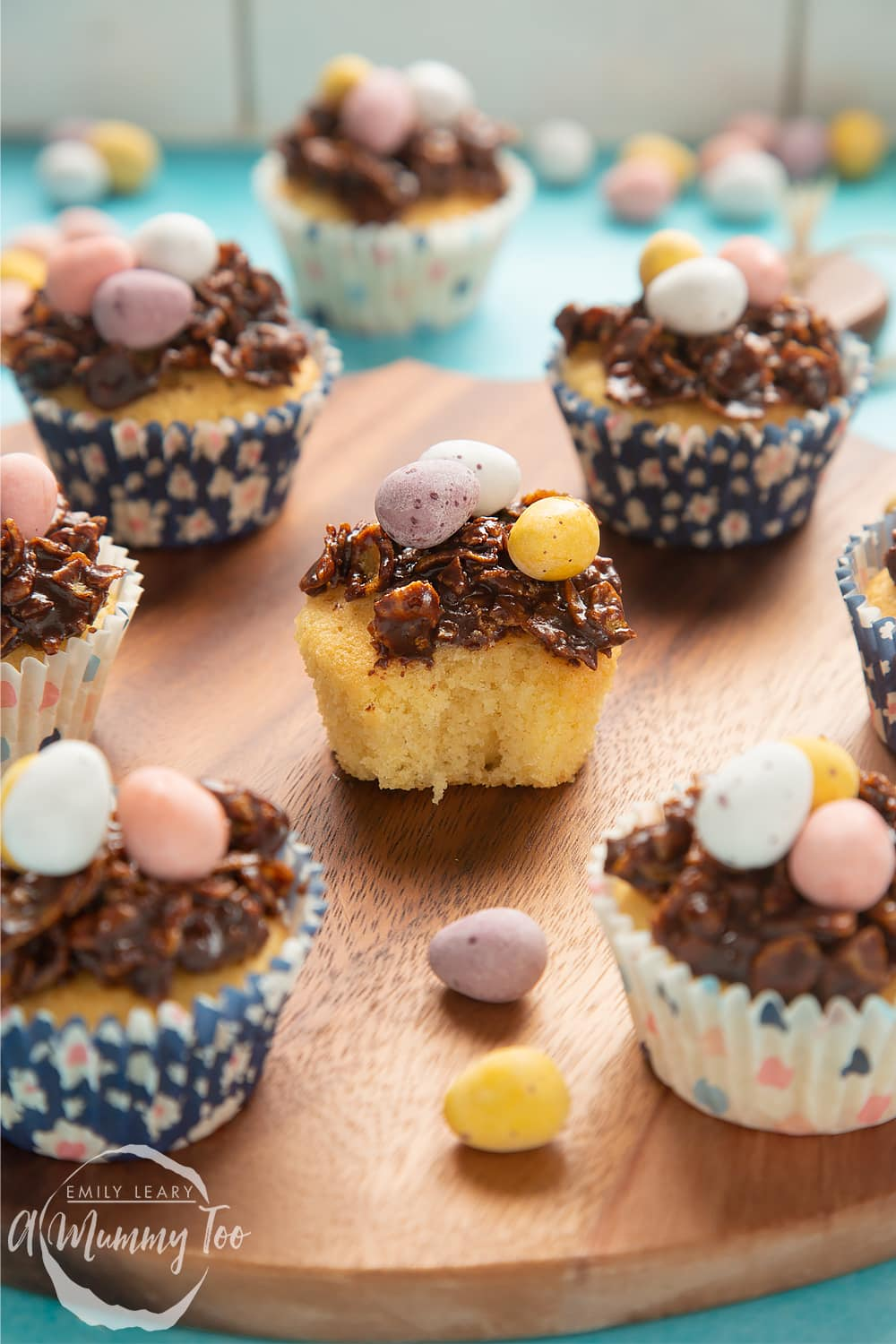 Front angle shot of easter nest cupcakes served on a wooden plate with a mummy too logo in the lower-left corner.