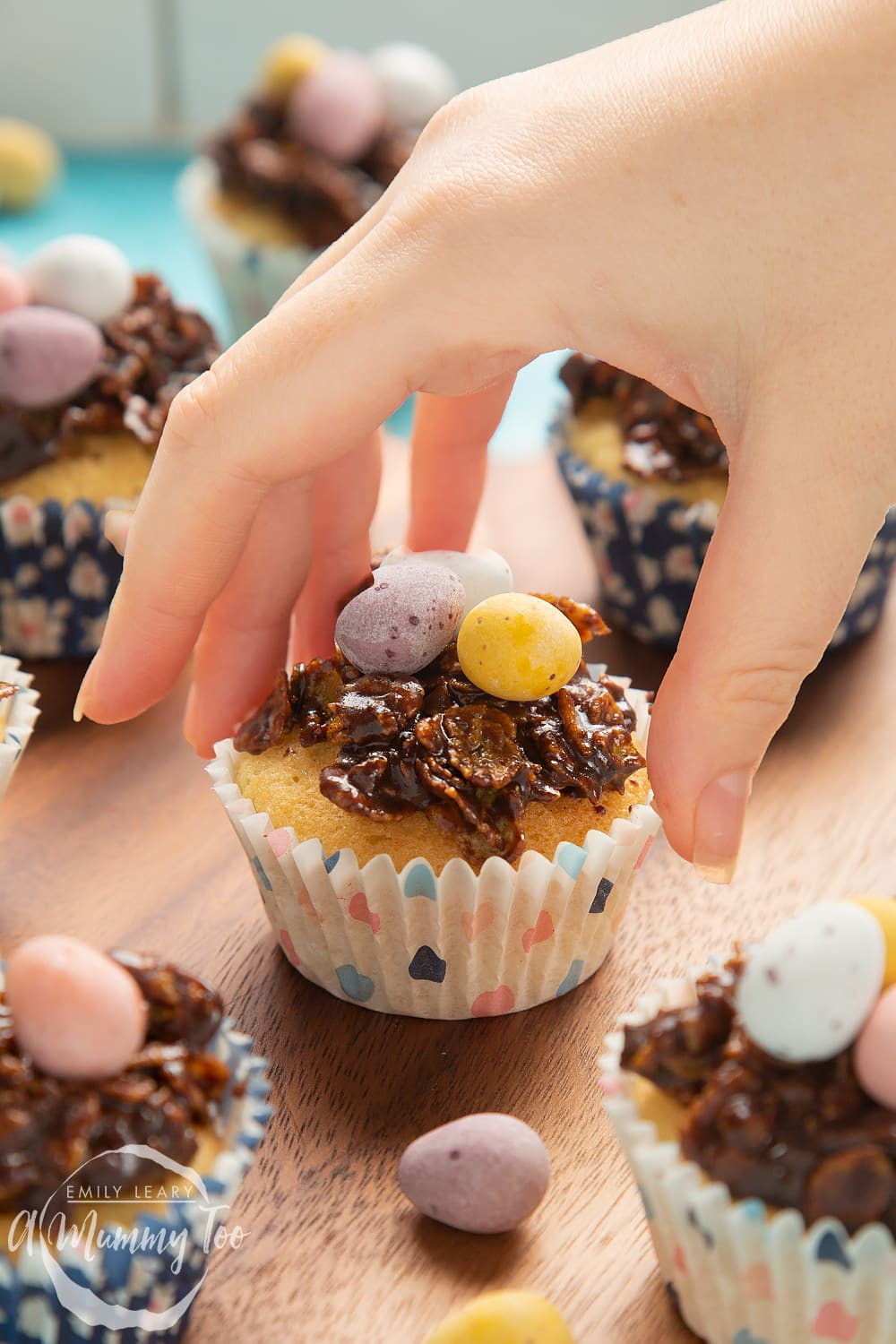 Front angle shot of hand holding a Easter nest cupcake with a mummy too logo in the lower-left corner