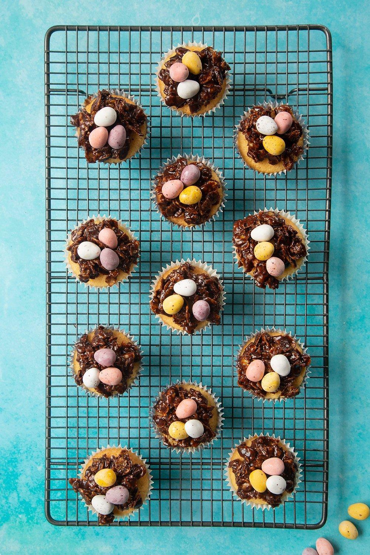 Adding three mini eggs to the top of the cornflake nesk cupcakes.