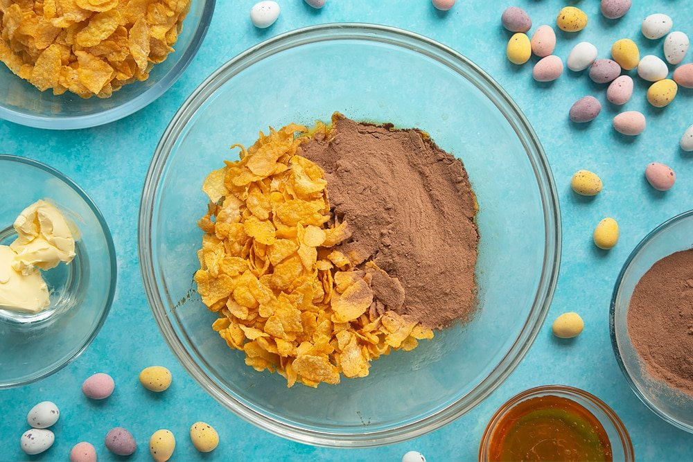 Overhead shot of chocolate and cornflakes in a glass mixing bowl.