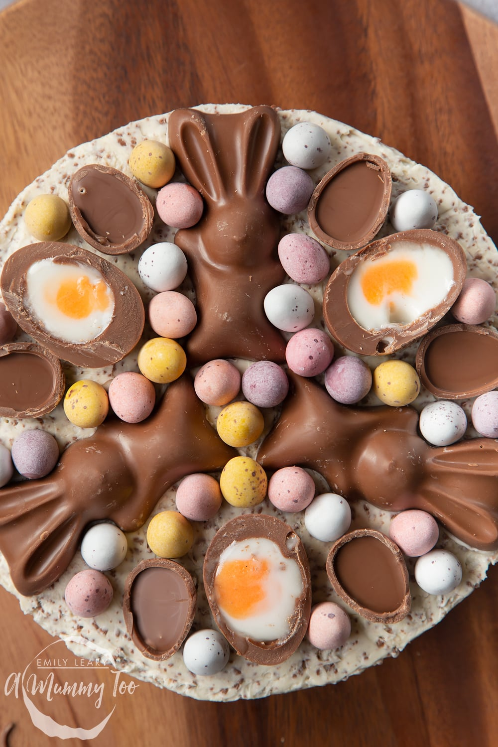 Close up from above of a no-bake Easter cheesecake. The cheesecake is topped with mini chocolate eggs, creme eggs and chocolate bunnies.