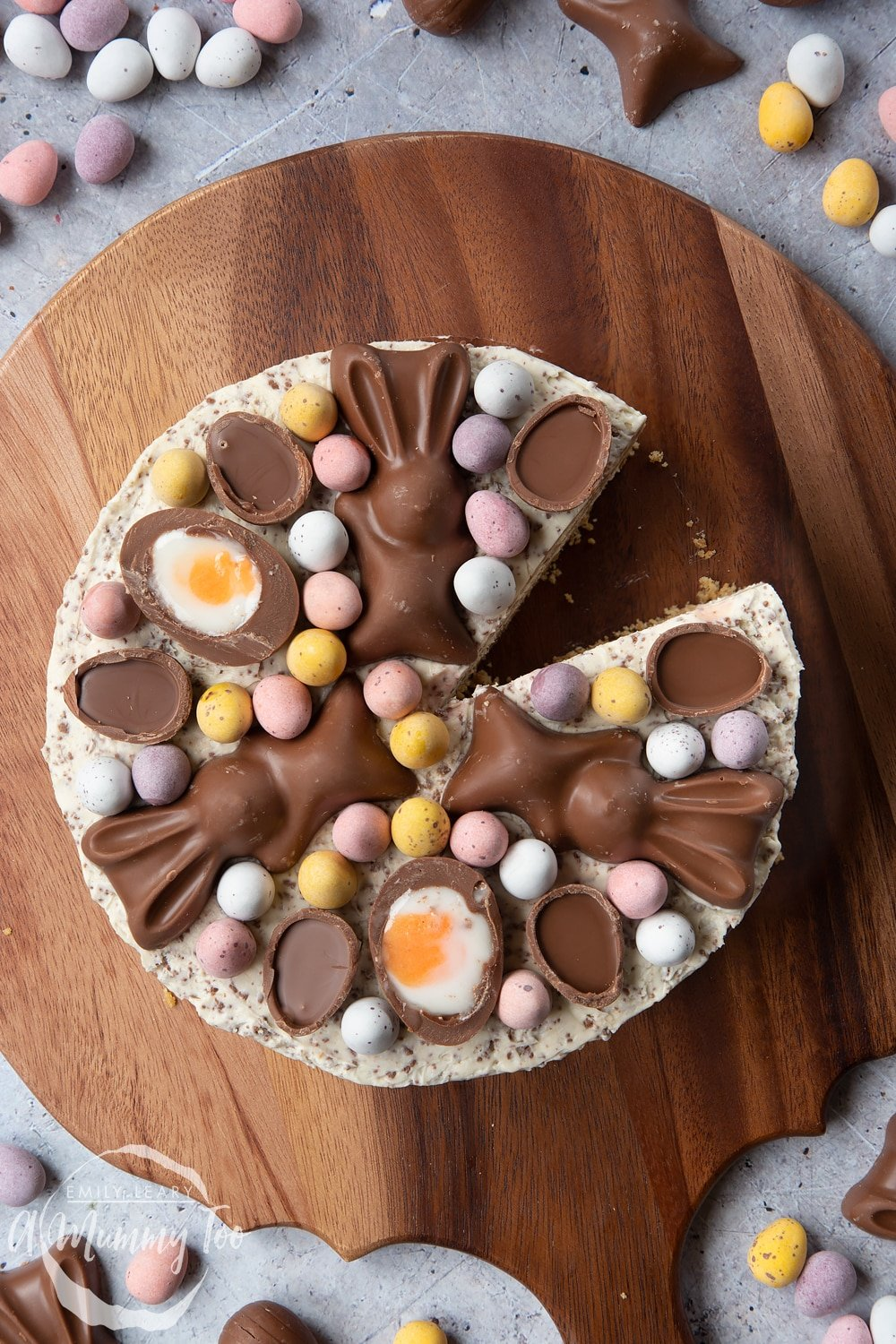No-bake Easter cheesecake shown from above. The cheesecake is topped with mini chocolate eggs, creme eggs and chocolate bunnies. The cheesecake sits on a wooden board and has a slice taken from it.