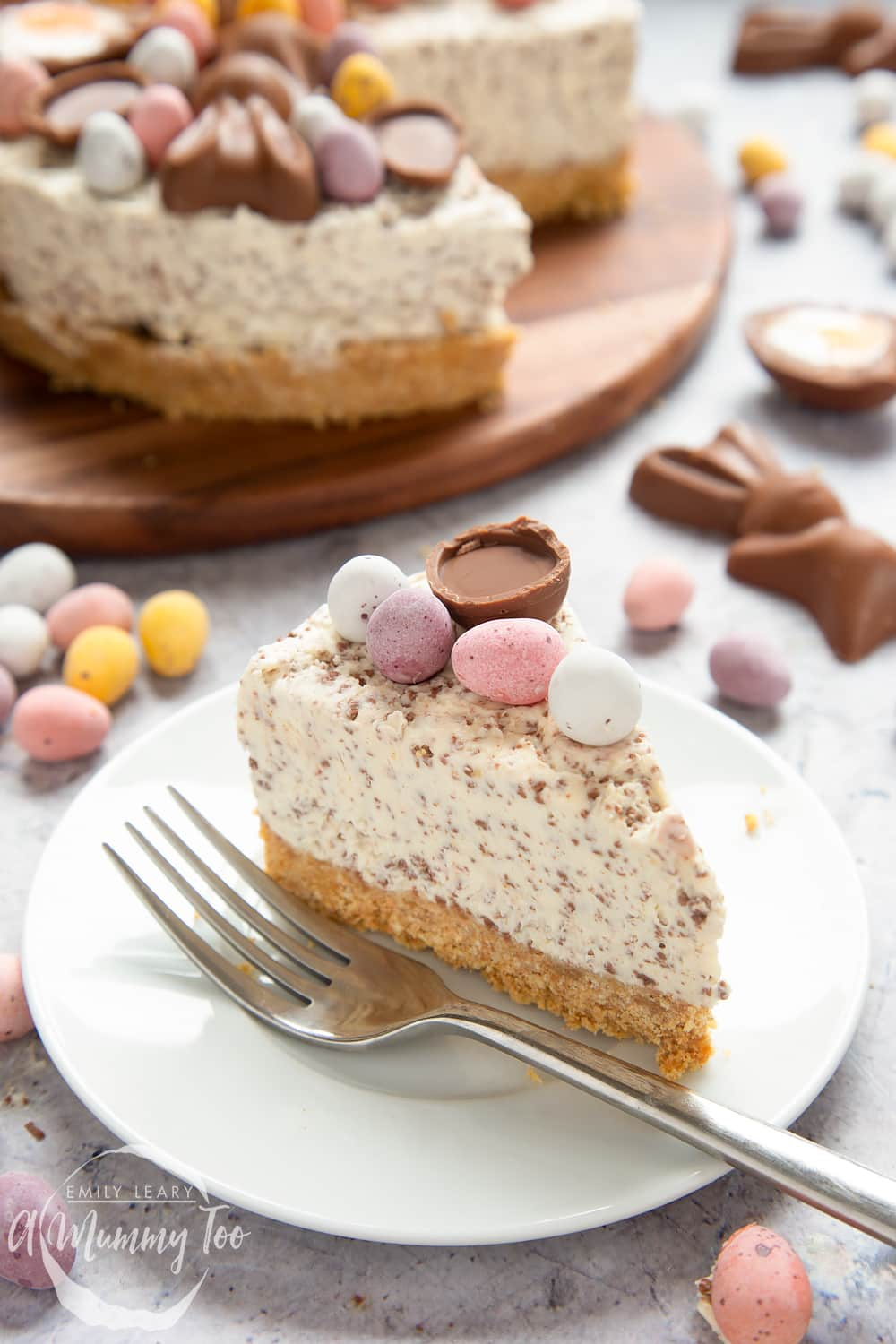 A slice of no-bake Easter cheesecake on a white plate with a fork beside it. The cheesecake is topped with mini chocolate eggs. More cheesecake is visible in the background.