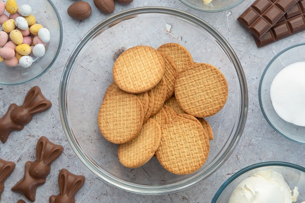 A glass bowl containing digestive biscuits. Around the bowl are ingredients to make no-bake Easter cheesecake.