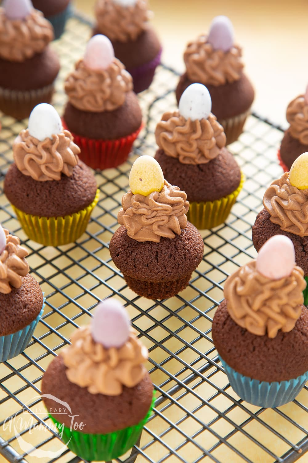 Front angle shot of a Mini chocolate cupcake for Easter topped with a mummy too logo in the lower-left corner