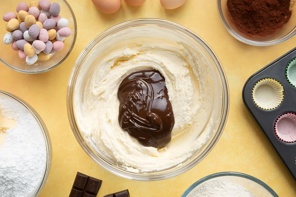 Overhead shot of frosting with melted dark chocolate in a large clear bowl