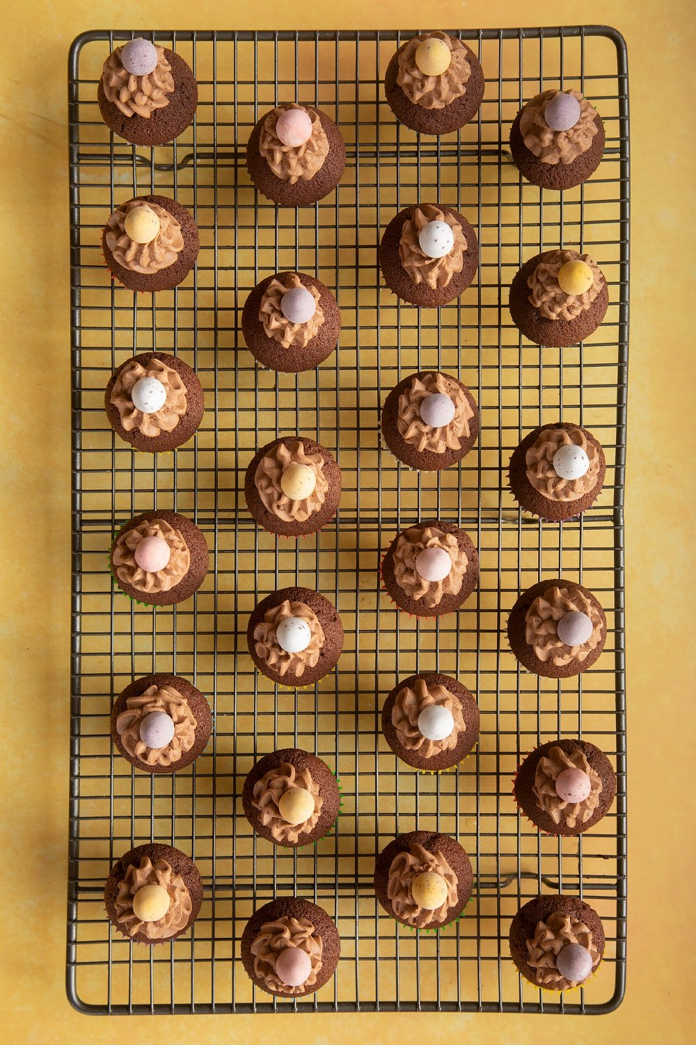 Overhead shot of chocolate muffins topped with chocolate frosting and mini chocolate egg on a baking rack