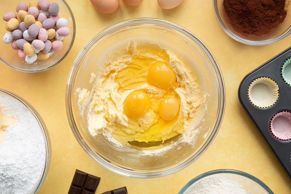 Overhead shot of margarine mix and three eggs in a large clear bowl