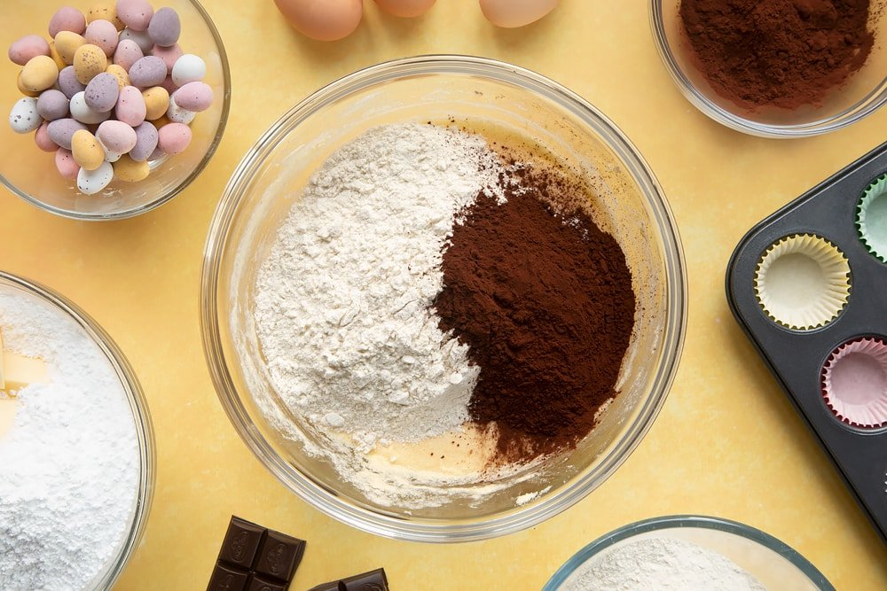 Overhead shot of flour and cocoa in a large clear bowl