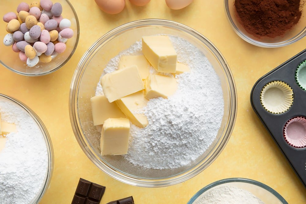 Overhead shot of butter and icing sugar in a large clear bowl