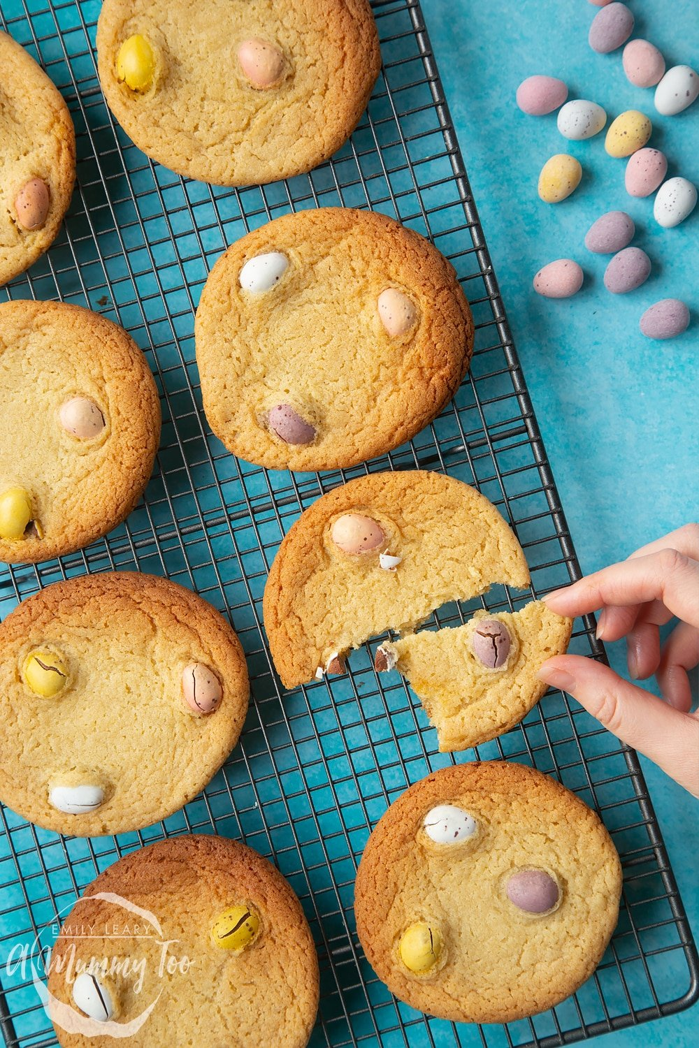 Overhead shot of a hand holding an Easter cookie with mini eggs with a mummy too logo in the lower-right corner
