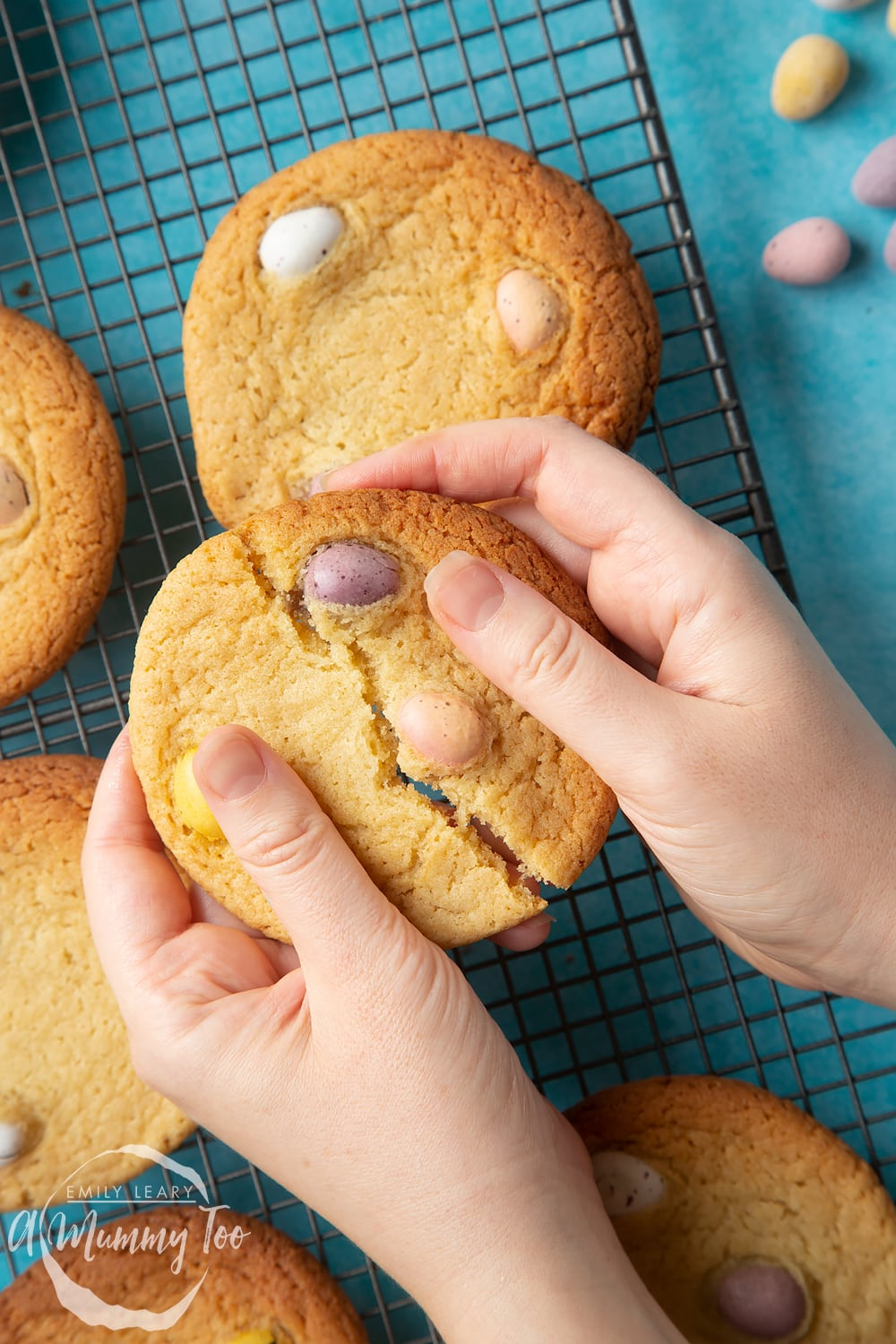 Overhead shot of a hand breaking open a Easter cookie with mini eggs with a mummy too logo in the lower-right corner