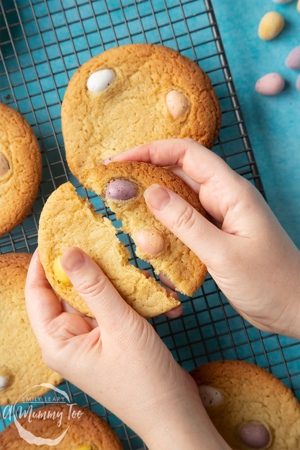 Overhead shot of a hand breaking a Easter cookie with mini eggs in half with a mummy too logo in the lower-left corner
