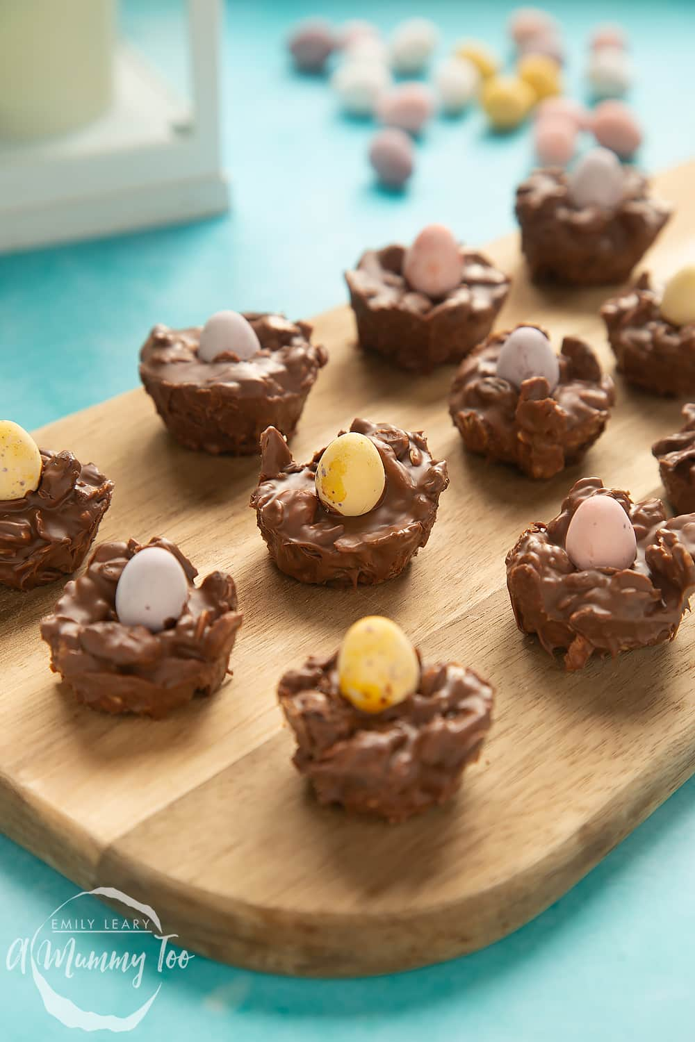Front angle shot of Crunchy, chewy, fruity muesli chocolate Easter nests served on a wooden board with a mummy too logo in the lower-left corner