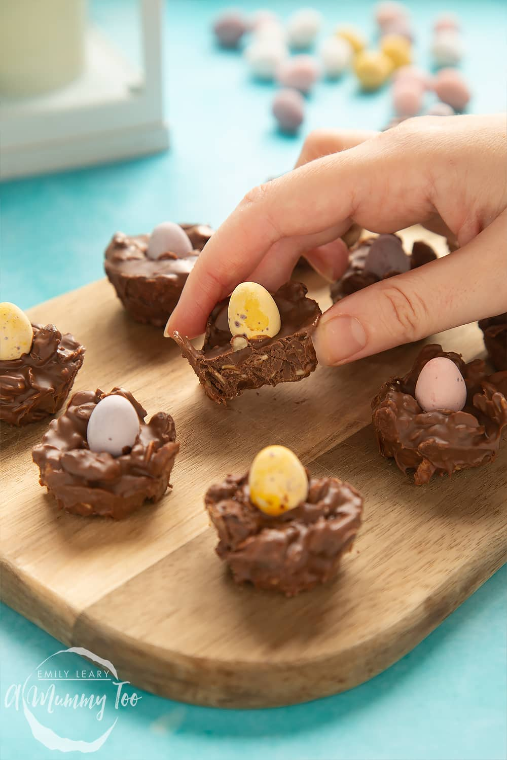 Side on shot of a hand holding a chocolate Easter nest cakes with an Easter egg