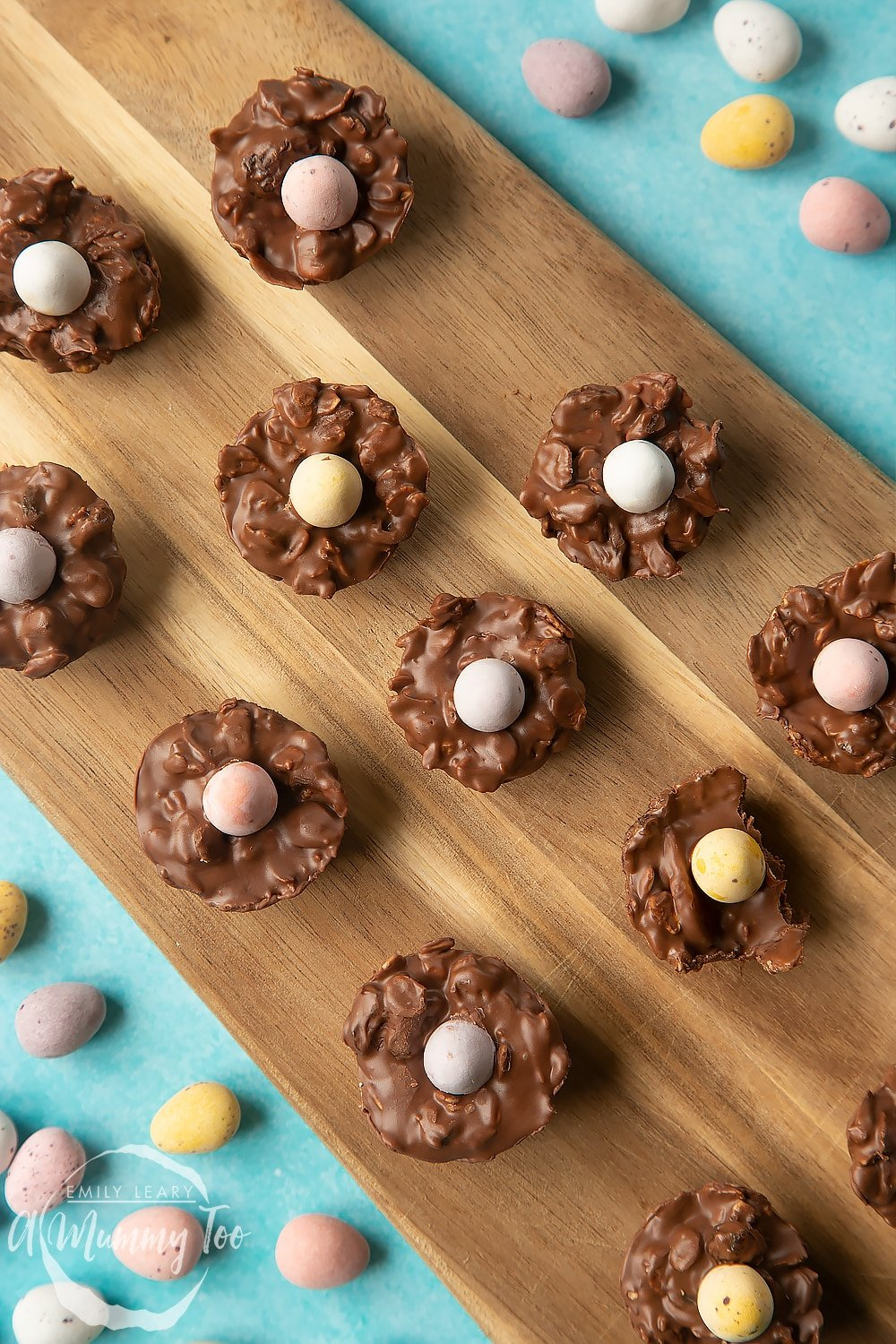 Overhead shot of a hand holding a chocolate Easter nest cakes on a wooden board.