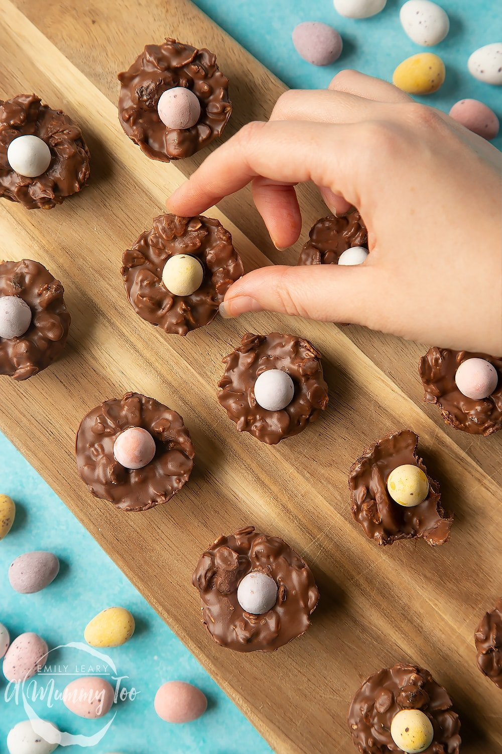Overhead shot of a hand holding a chocolate Easter nest cakes with an Easter egg