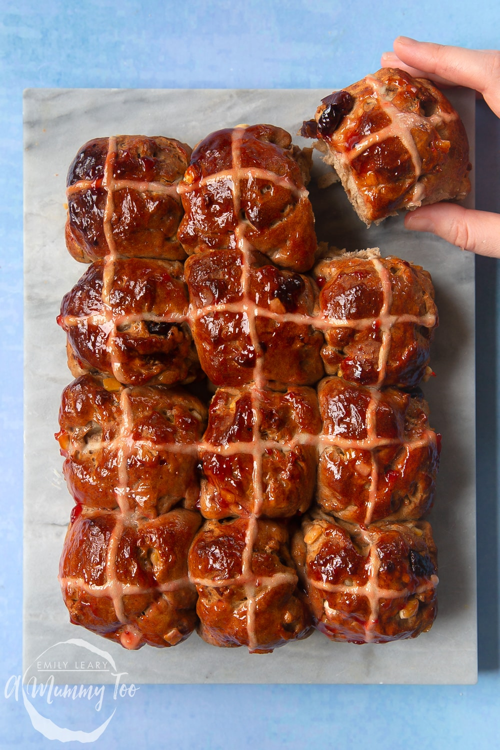 12 vegan hot cross buns on a marble board. A hand reaches in to take one.