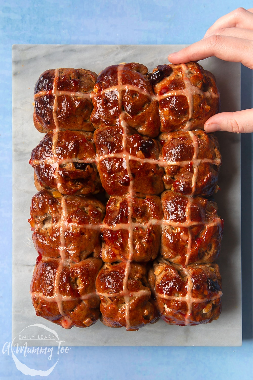 12 vegan hot cross buns on a marble board. A hand reaches in as if to take one.