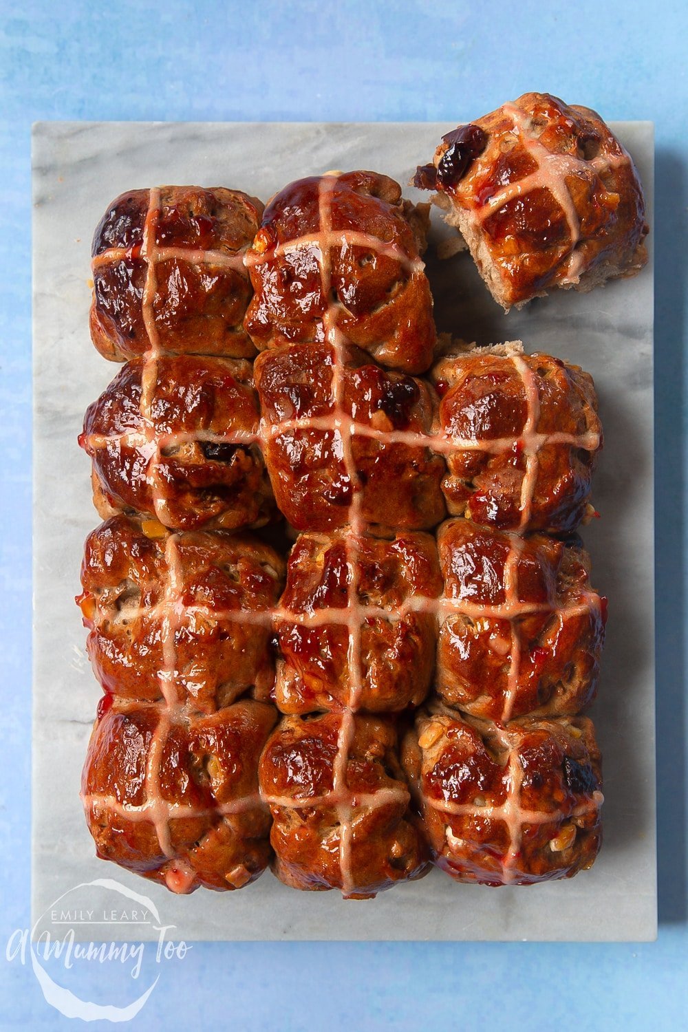12 vegan hot cross buns on a marble board. One is lifted away from the others.