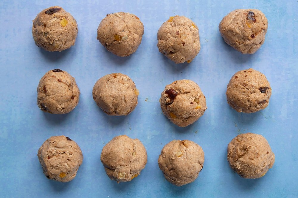 Vegan hot cross buns dough with mixed peel and chopped dates, divided into 12 balls.