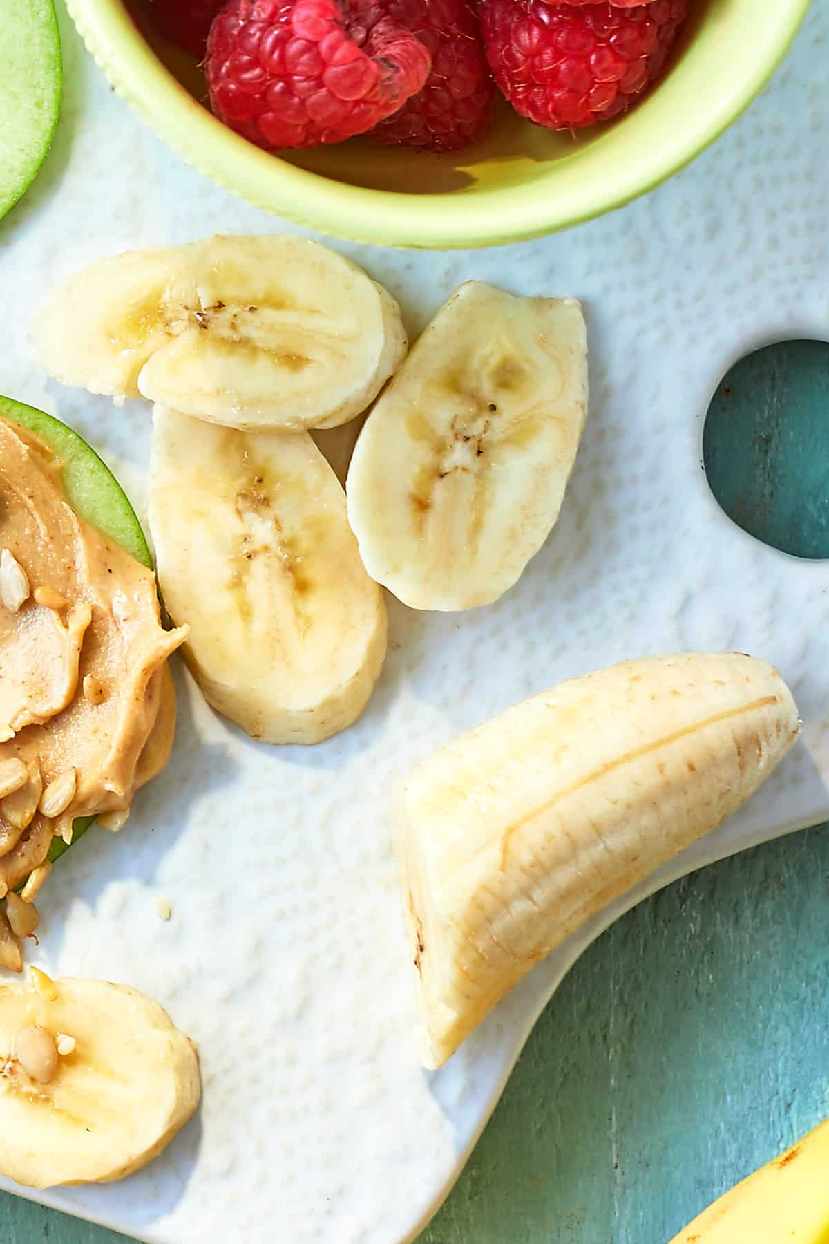 Sliced banana on a white board, surrounded by ingredients for apple slices with peanut butter.