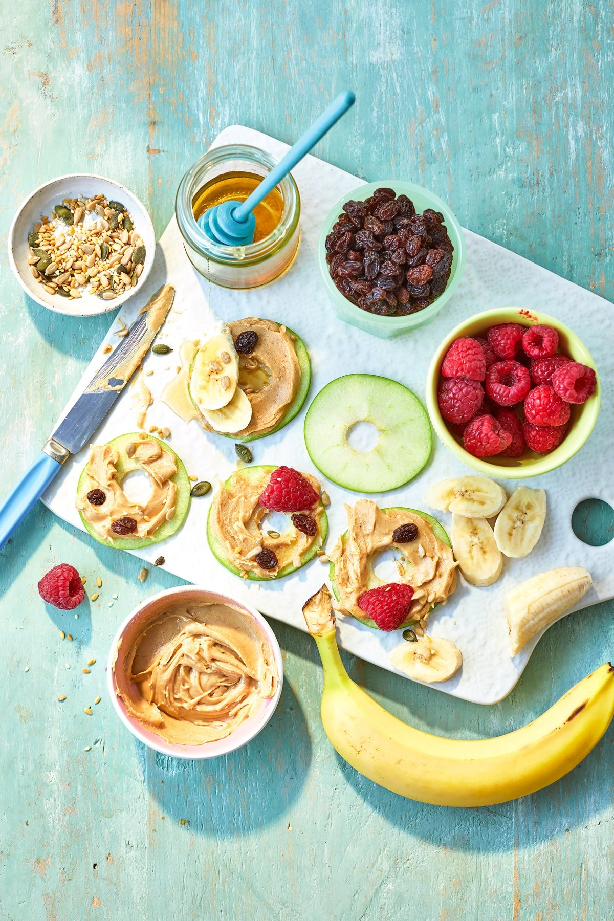 Apple slices with peanut butter on a white board, surrounded by topping ingredients such as raspberries, seeds, honey and banana slices.