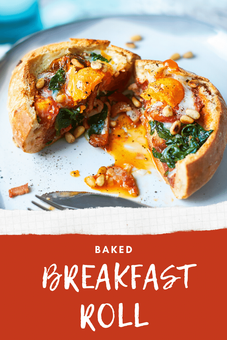 A breakfast roll on a white plate. It is filled with sausage, bacon, spinach, tomatoes and pine nuts, topped with an egg. The roll is cut open to reveal the runny egg yolk. The caption reads: Baked breakfast roll