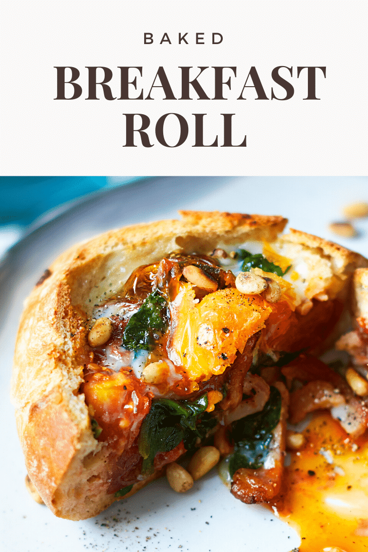 A breakfast roll on a white plate. It is filled with sausage, bacon, spinach, tomatoes and pine nuts, topped with an egg. The caption reads: Baked breakfast roll
