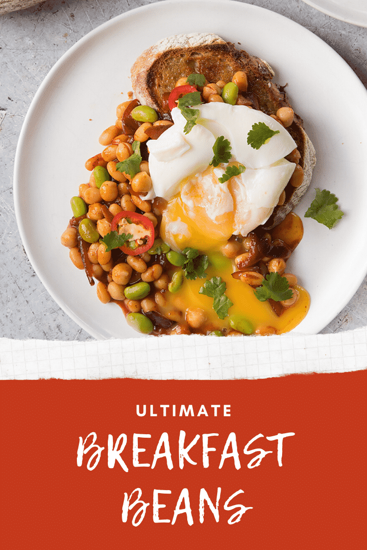 Breakfast beans with chilli, chickpeas and edamame served on sour dough toast with a poached egg on top, the yolk running onto the plate. Caption reads: ultimate breakfast beans.