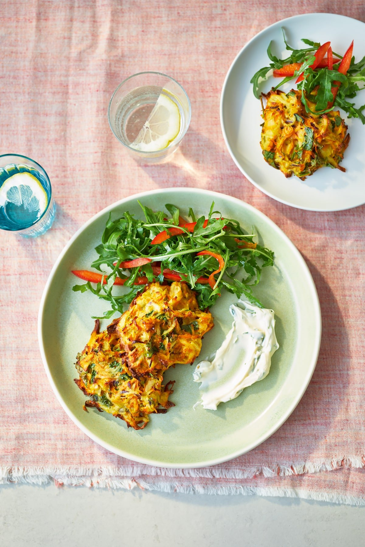 Two plates topped with carrot patties and a rocket and pepper salad.
