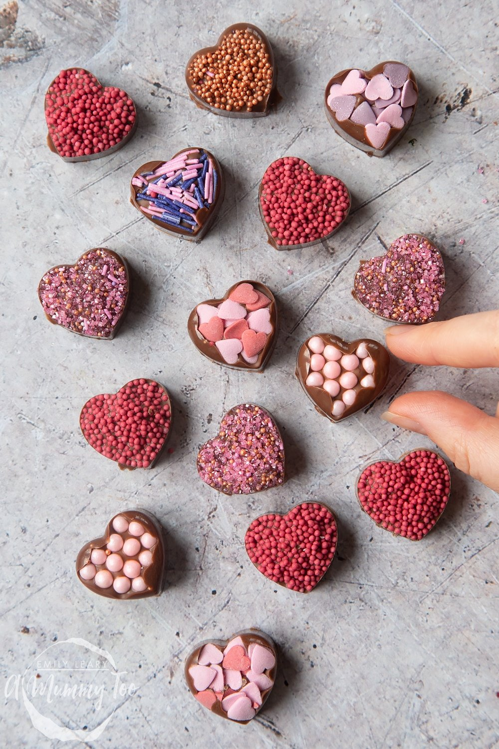 Overhead shot of a hand touching a chocolate heart with pink sprinkles with a mummy too logo in the lower-left corner