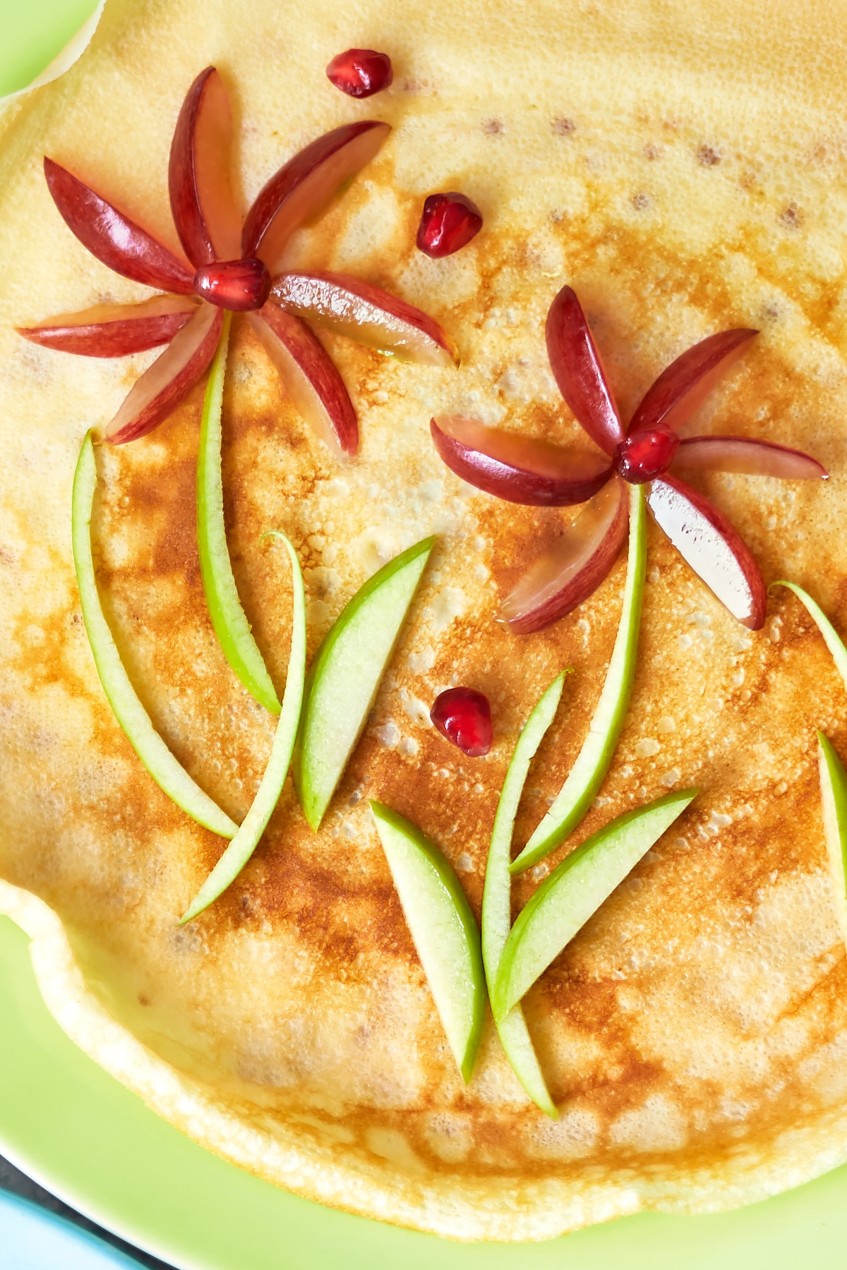 A crepe-style pancake is decorated with fruit to resemble flowers.