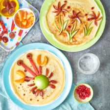 overhead view of 2 plates with crepe like pancakes with a crab and flower designs made out of vegetables.