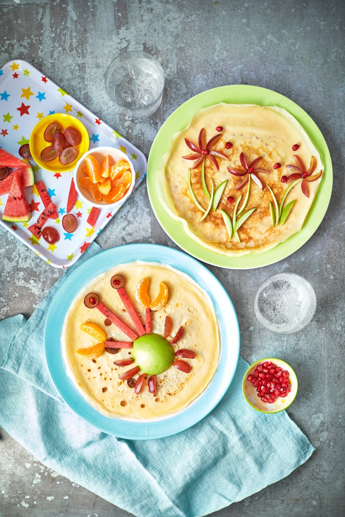 Two crepe-style pancakes on coloured plates. Both pancakes are decorated with fruit, one to resemble a crab and the other to resemble flowers. Further chopped fruit is shown on tray, to be used to create fun pancake ideas