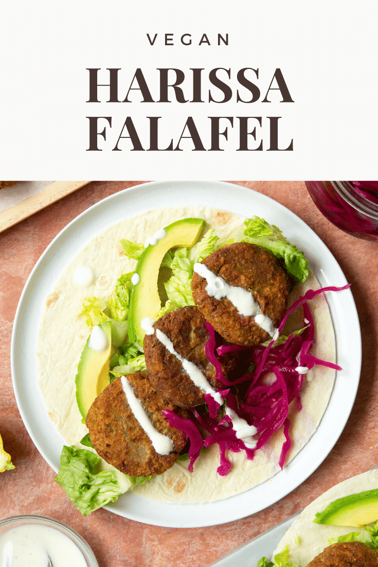 A harissa falafel wrap arranged on a plate with pickled cabbage and salad, drizzled with tahini dressing. The text caption reads, vegan harissa falafel.