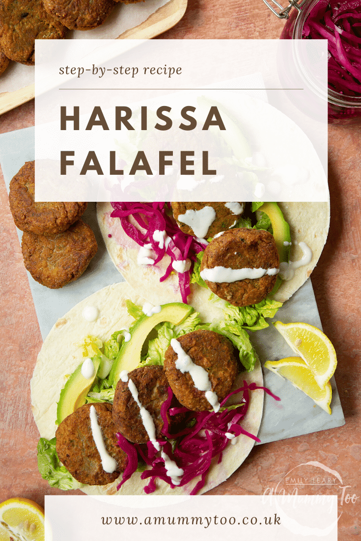 Two harissa falafel wraps arranged on a marble board with pickled cabbage and salad, drizzled with tahini dressing. The text caption reads, harissa falafel.