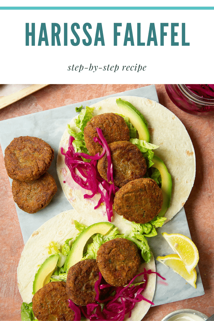 Two harissa falafel wraps arranged on a marble board with pickled cabbage and salad. The text caption reads, harissa falafel.