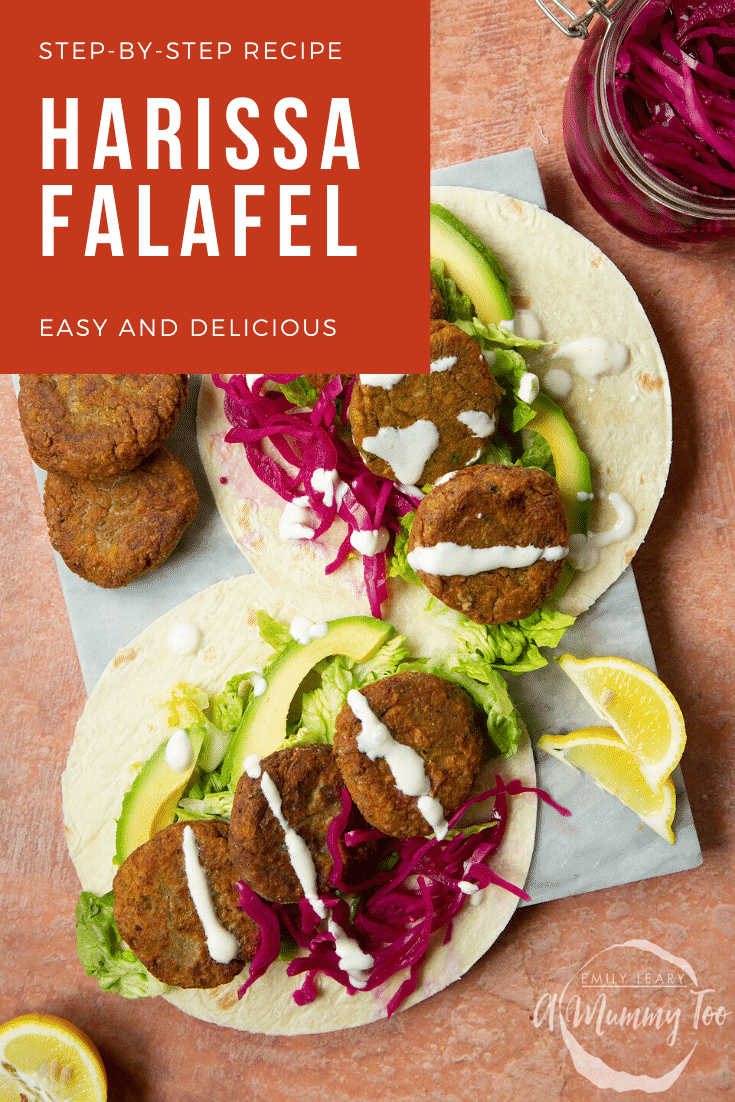 Two harissa falafel wraps arranged on a marble board with pickled cabbage and salad, drizzled with tahini dressing. The text caption reads, harissa falafel - easy and delicious.