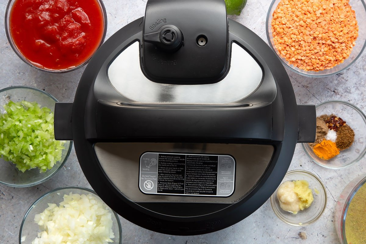 Overhead shot of slow cooker with its lid on surrounded by ingredients in clear bowls