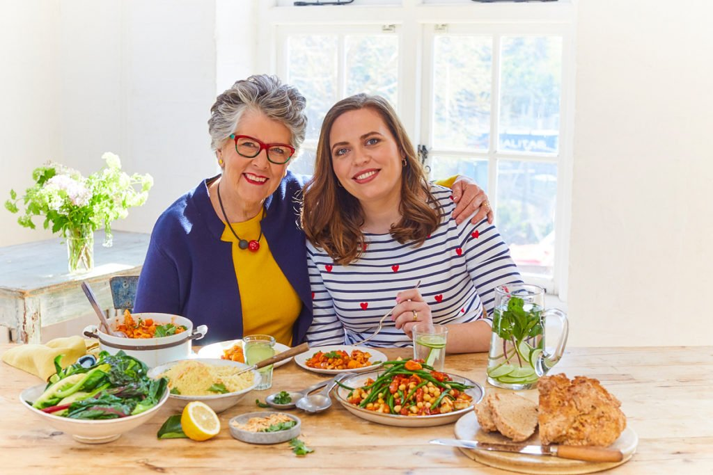 Prue Leith and Peta Leith sitting at a dinner table with dishes from The Vegetarian Kitchen