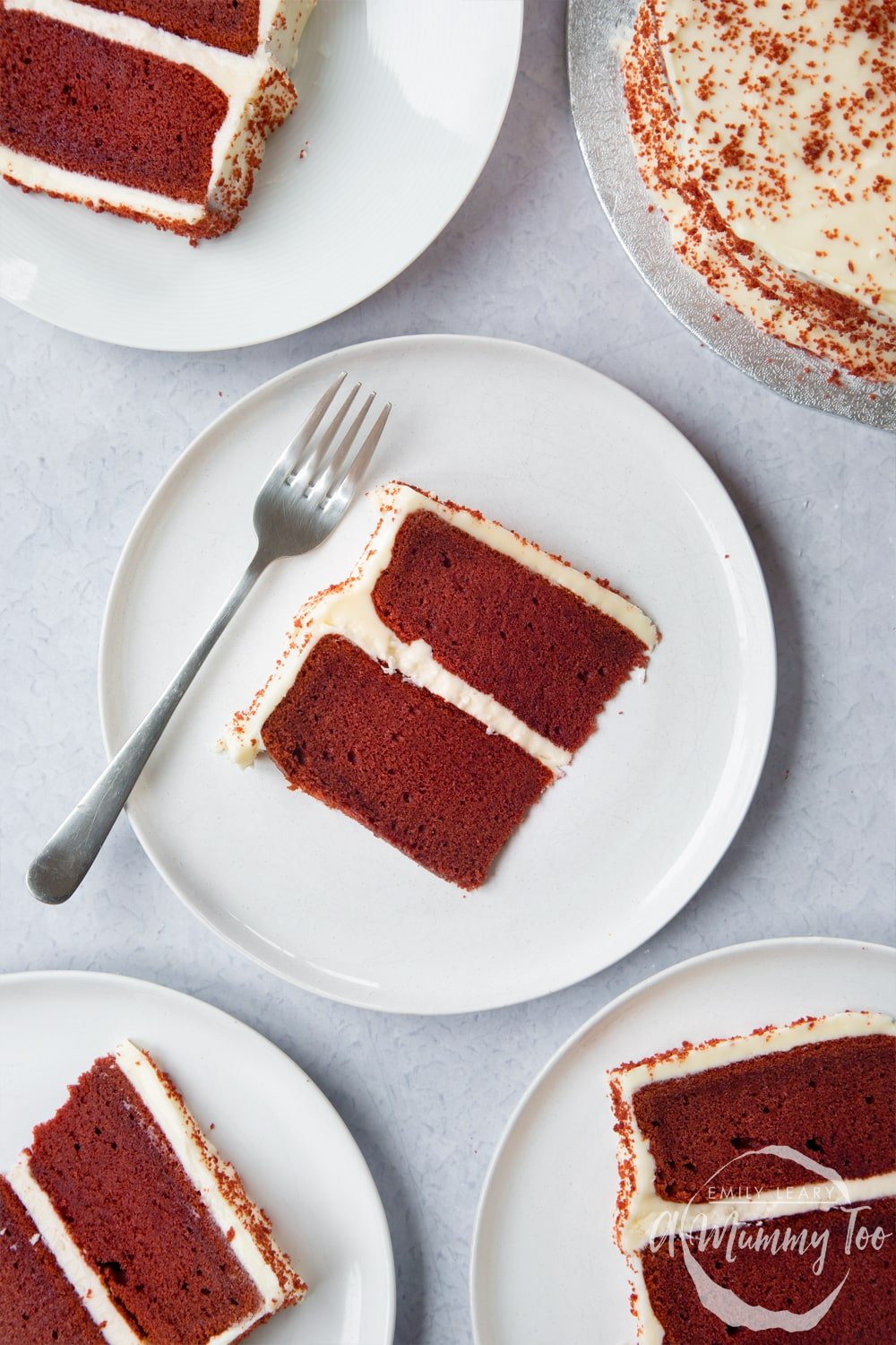 A slice of filled red velvet cake on a white plate. A fork rests on the plate. More slices of cake are shown to the edges of the frame.