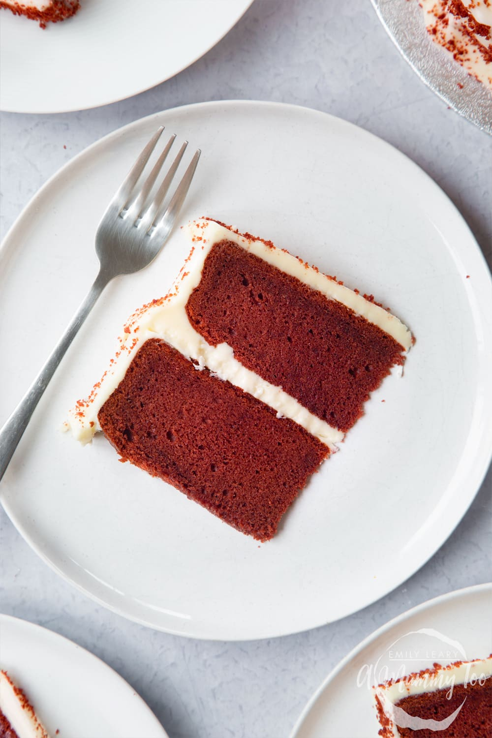 A slice of filled red velvet cake on a white plate. A fork rests on the plate.