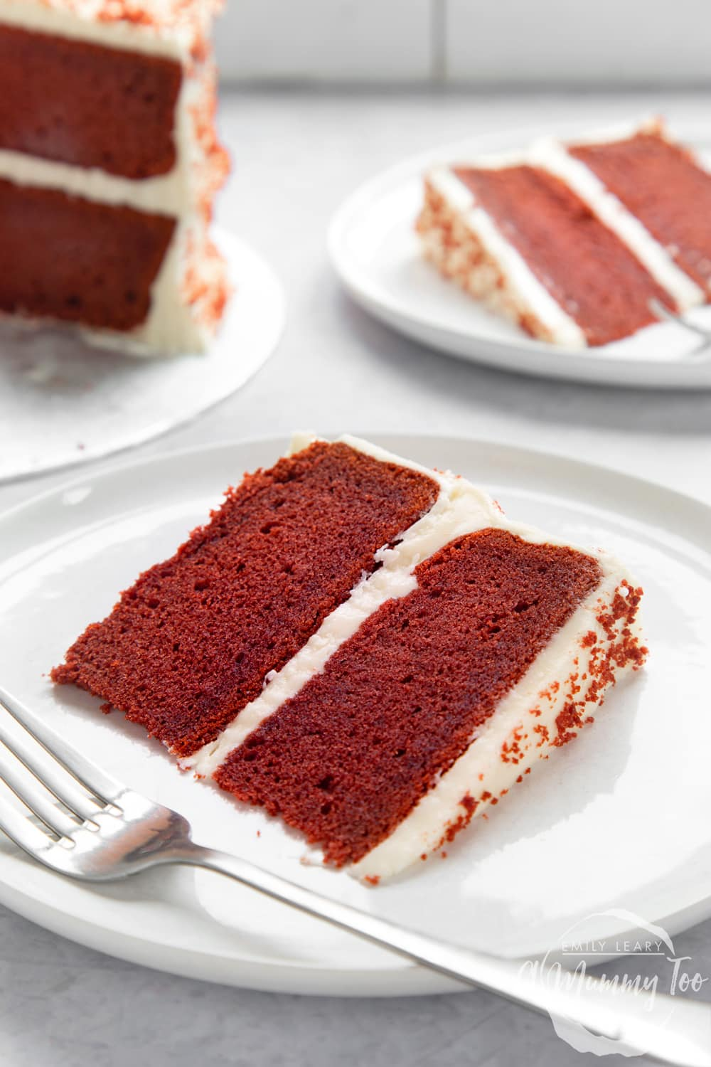 A slice of filled red velvet cake on a white plate. A fork rests on the plate. More cake is shown in the background.