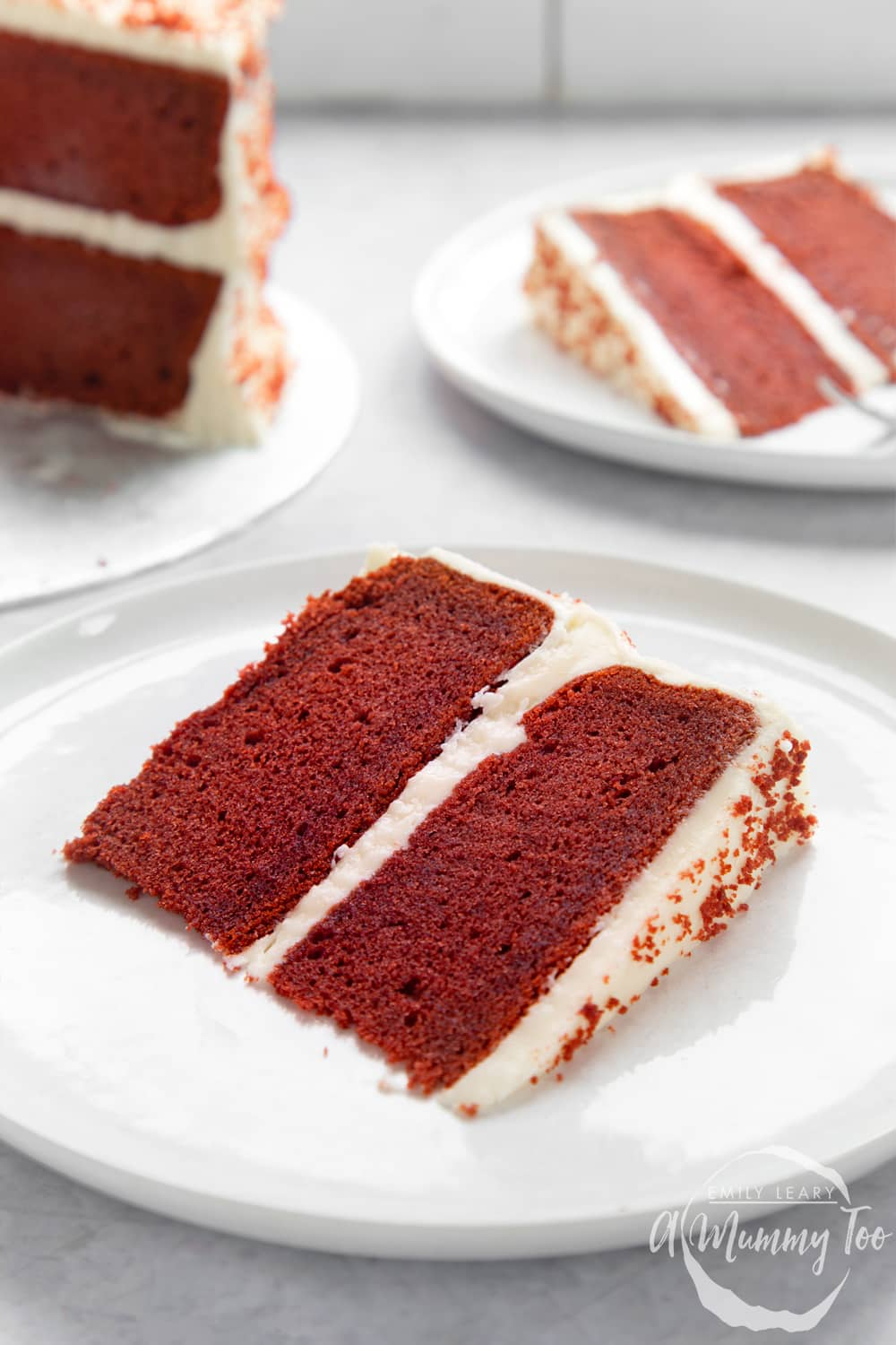 A slice of filled red velvet cake on a white plate. More cake is shown in the background.