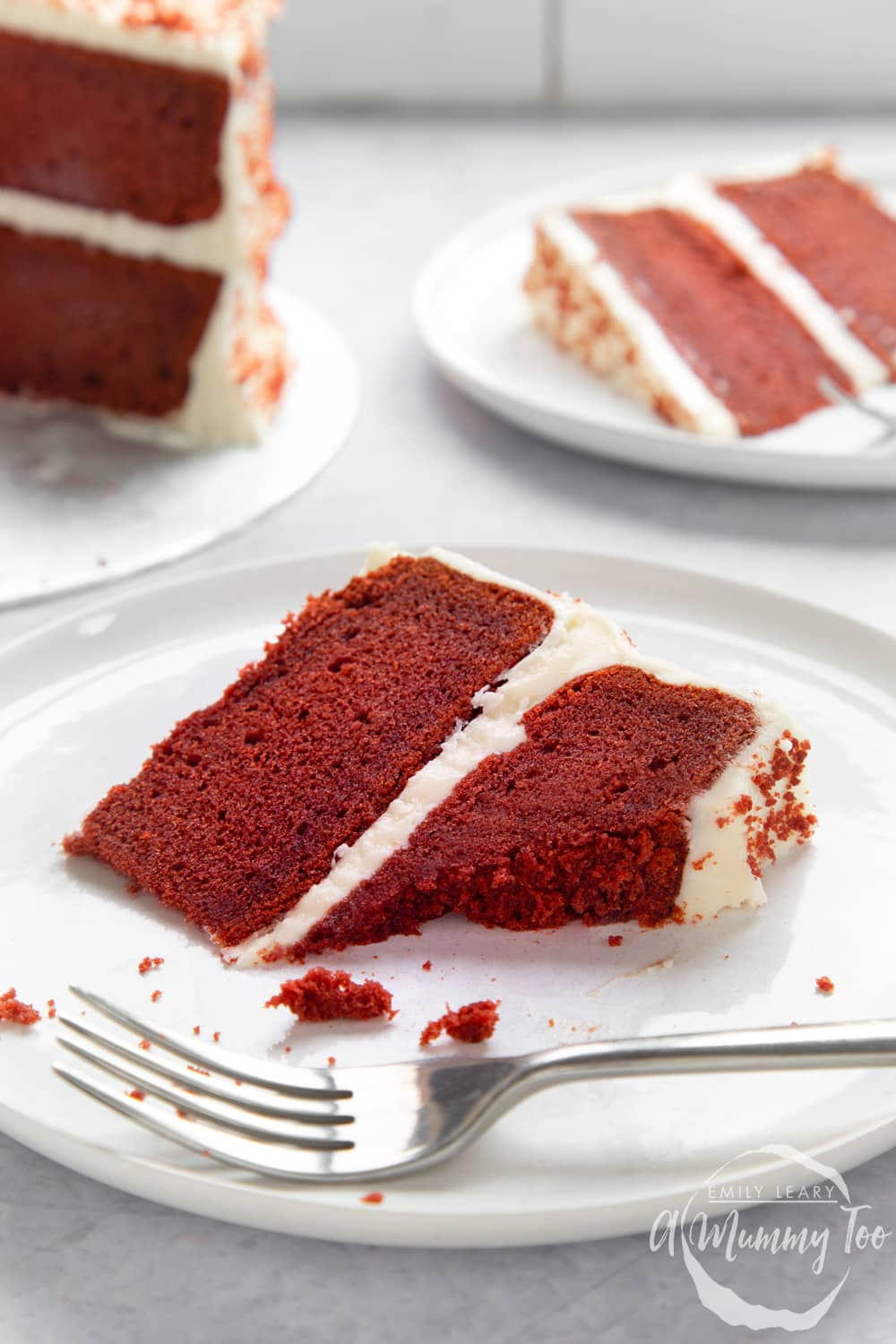 A slice of filled red velvet cake on a white plate. A fork rests on the plate. Some of the slice has been eaten. More cake is shown in the background.
